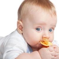 Малыш держит в руках соску желтого цвета