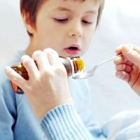 Мальчик в голубом свитере готов пить жаропонижающее