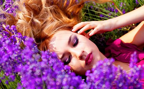 Девушка с рыжими волосами лежит среди цветов лаванды