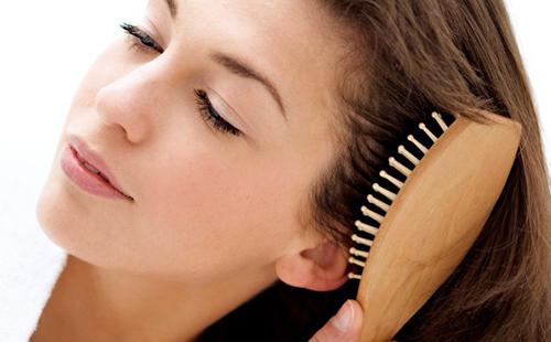 Девушка расчёсывает волосы деревянной массажной щёткой