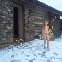 Весёлая малявка стоит прямо на снегу