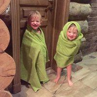 Двое смеющихся ребятишек завернулись в зелёные полотенца